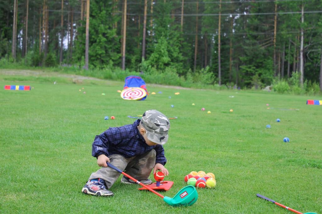 Nuori golfari asettaa pallon huolellisesti tiin päälle ennen lyöntiä.